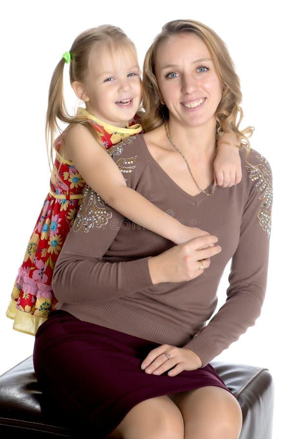 A mãe e a filha pequena abraçam delicadamente imagem de stock