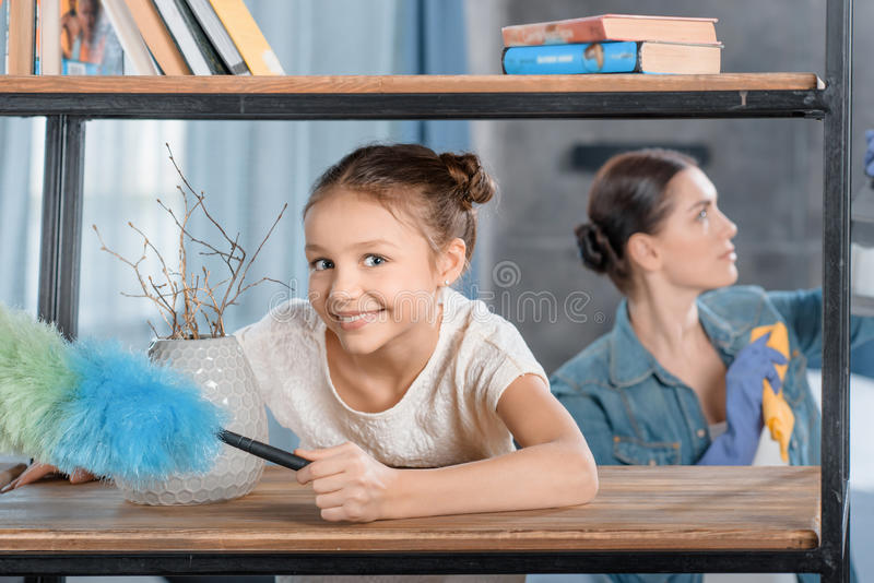 Mãe e filha pequena com casa da limpeza do espanador fotografia de stock royalty free