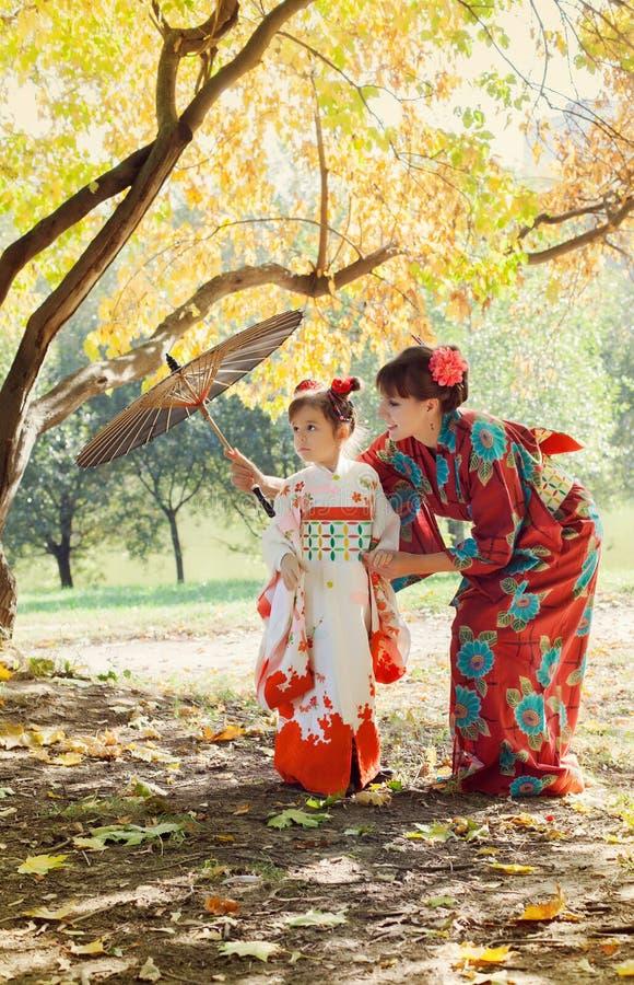 Mãe e filha pequena em um quimono imagens de stock