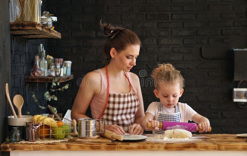 A mãe e a filha preparam cookies na cozinha imagens de stock royalty free