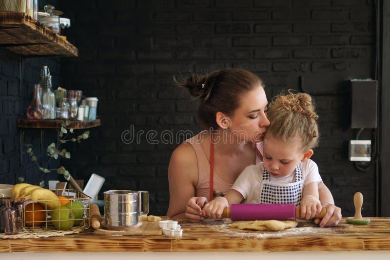 A mãe e a filha preparam cookies na cozinha fotos de stock