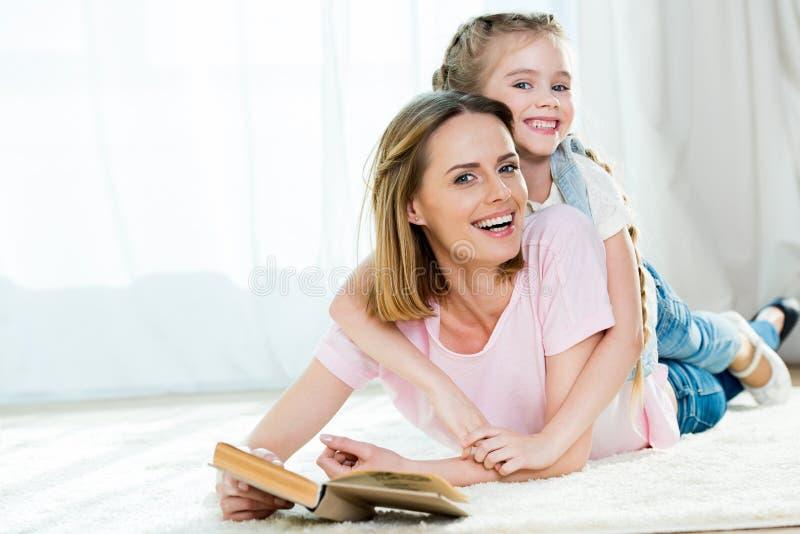 Mãe e filha que abraçam ao encontrar-se no tapete e no livro de leitura foto de stock