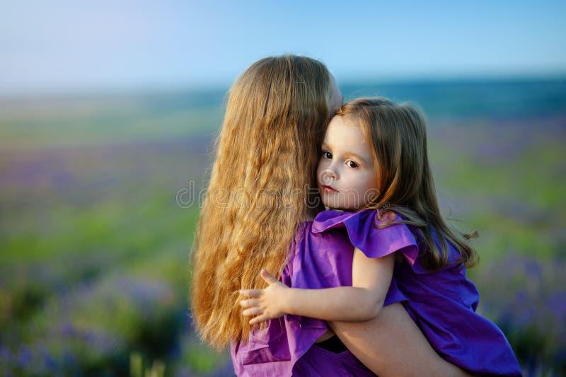 Mãe e filha que abraçam no amor que joga no parque fotografia de stock royalty free