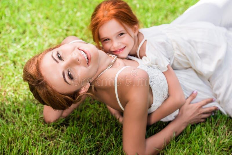 Mãe e filha que abraçam no parque imagens de stock