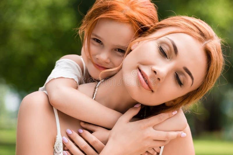 Mãe e filha que abraçam no parque foto de stock royalty free