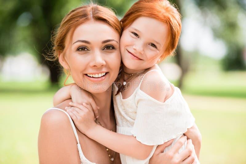 Mãe e filha que abraçam no parque imagens de stock royalty free