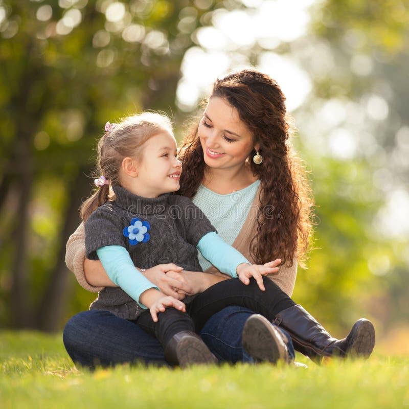 A mãe e a filha que andam no outono estacionam Cena da natureza da beleza com fundo colorido, as árvores amarelas e as folhas na  imagem de stock royalty free
