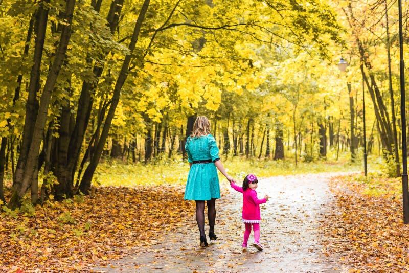 A mãe e a filha que andam no outono estacionam, vista traseira fotos de stock royalty free