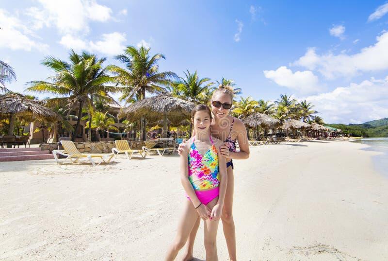 A mãe e a filha que apreciam uma praia tropical vacation fotos de stock