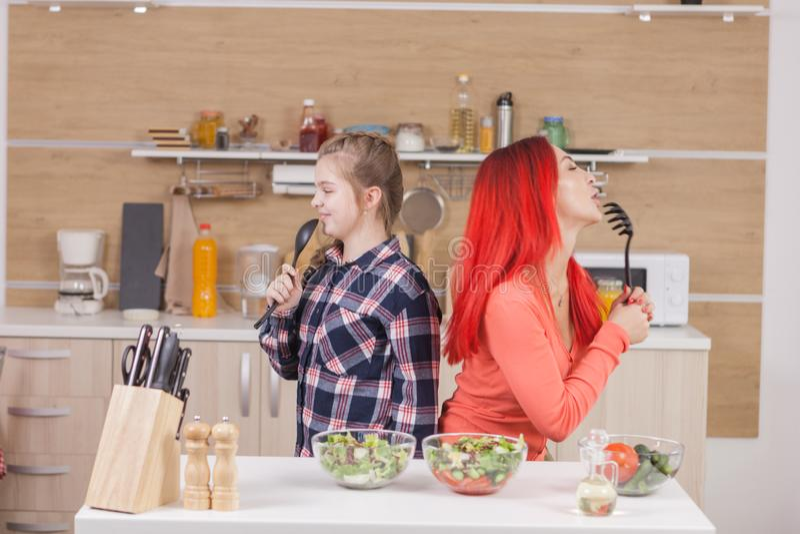 Mãe e filha que cantam em intruments da cozinha fotografia de stock royalty free