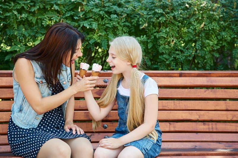 Mãe e filha que comem o gelado em um parque que senta-se em um banco fotografia de stock