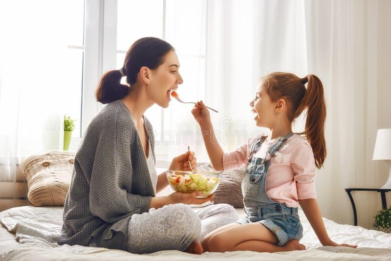 Mãe e filha que comem a salada fotos de stock royalty free