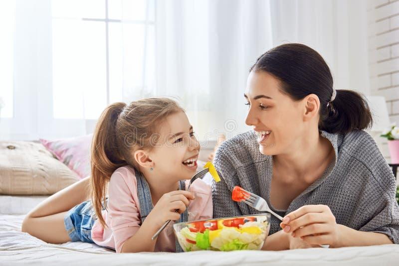 Mãe e filha que comem a salada foto de stock royalty free