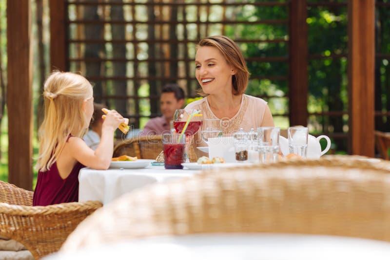 Mãe e filha que comem sanduíches saborosos fora fotografia de stock royalty free