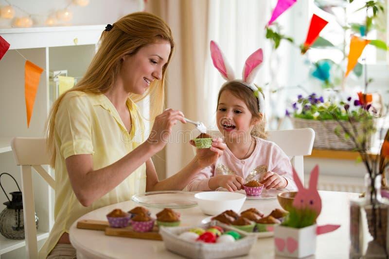 Mãe e filha que comemoram a Páscoa, cozinhando queques, imagem de stock