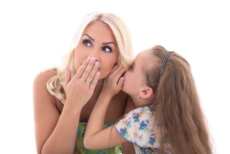 Mãe e filha que compartilham de um sussurro do segredo isolado no whit fotos de stock
