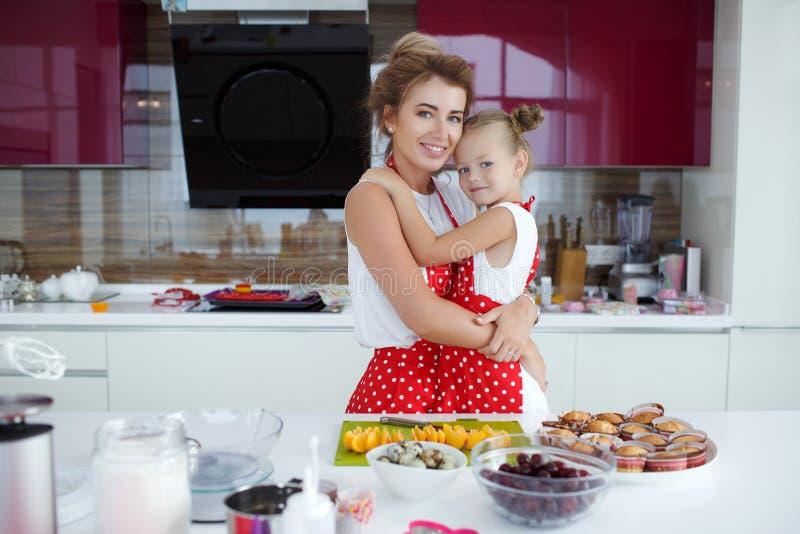 Mãe e filha que cozinham queques na tabela festiva fotografia de stock