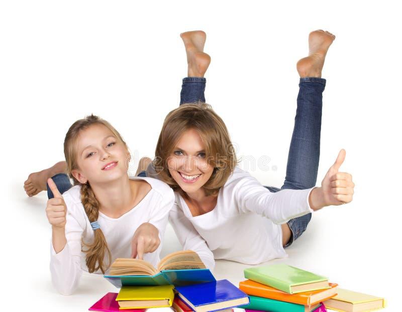 Mãe e filha que deitam livros de leitura fotografia de stock