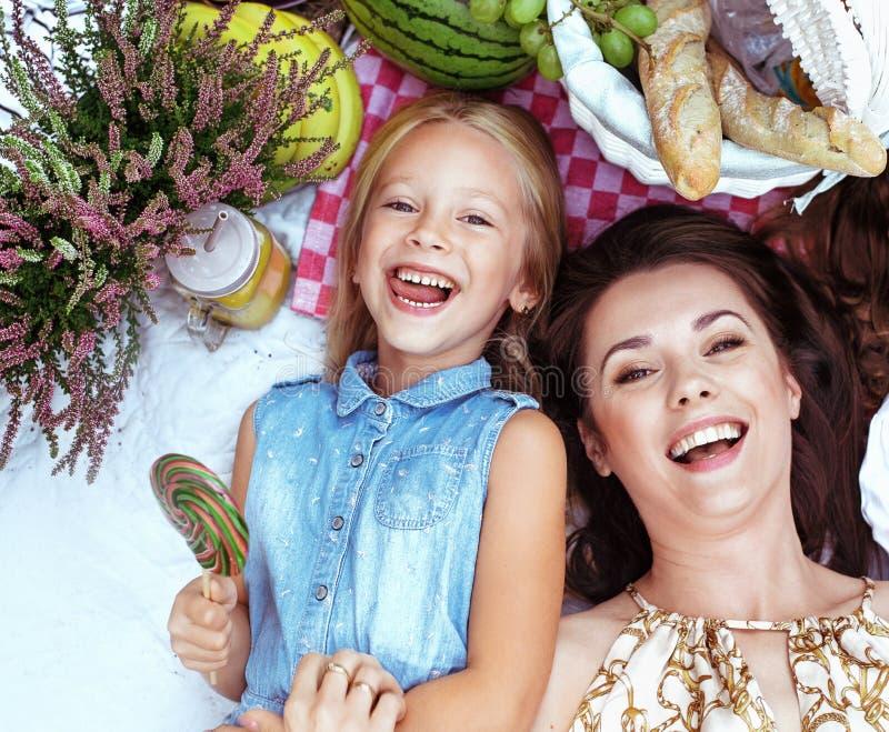 Mãe e filha que encontram-se em uma cobertura do piquenique fotos de stock
