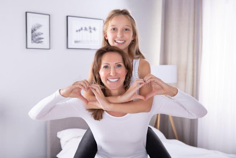 M?e e filha que fazem a forma do cora??o imagem de stock royalty free