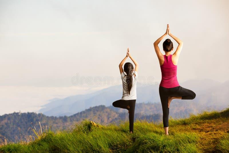 Mãe e filha que fazem a ioga imagens de stock