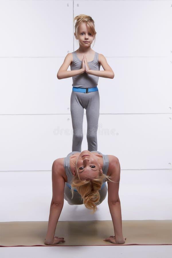 A mãe e a filha que fazem a ioga exercitam, aptidão, gym que veste a mesma mulher emparelhada p da família dos fato de esporte es foto de stock