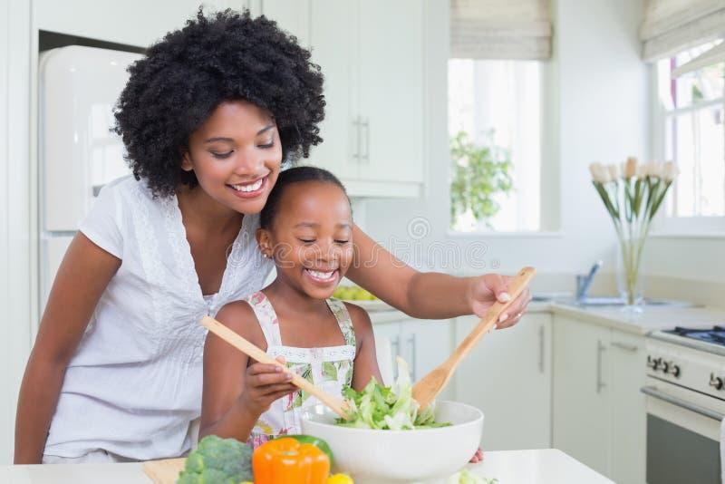 Mãe e filha que fazem uma salada junto fotos de stock royalty free