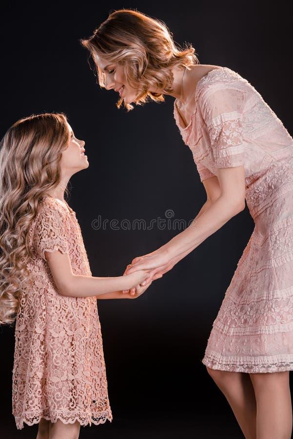 Mãe e filha que guardam as mãos e que olham se fotografia de stock