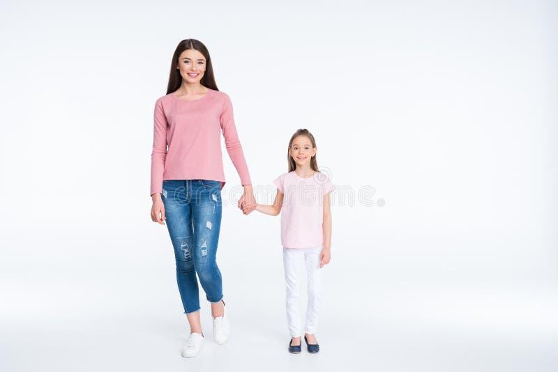 Mãe e filha que guardam as mãos no branco imagens de stock royalty free