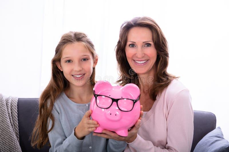 M?e e filha que guardam Piggybank foto de stock