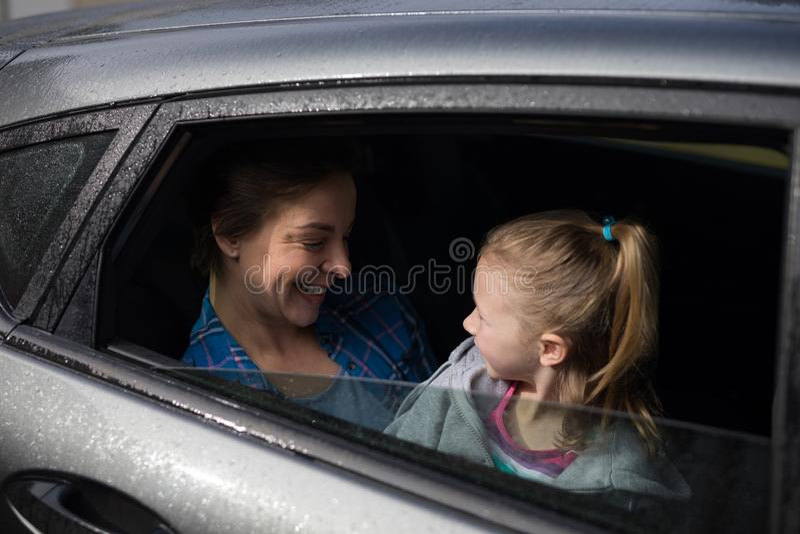 Mãe e filha que interagem na parte de trás do carro imagem de stock
