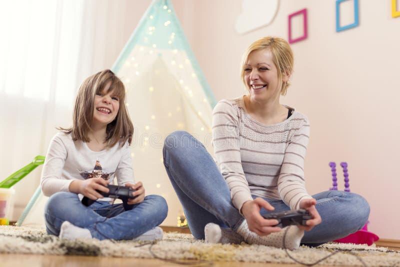 Mãe e filha que jogam jogos de vídeo imagens de stock royalty free
