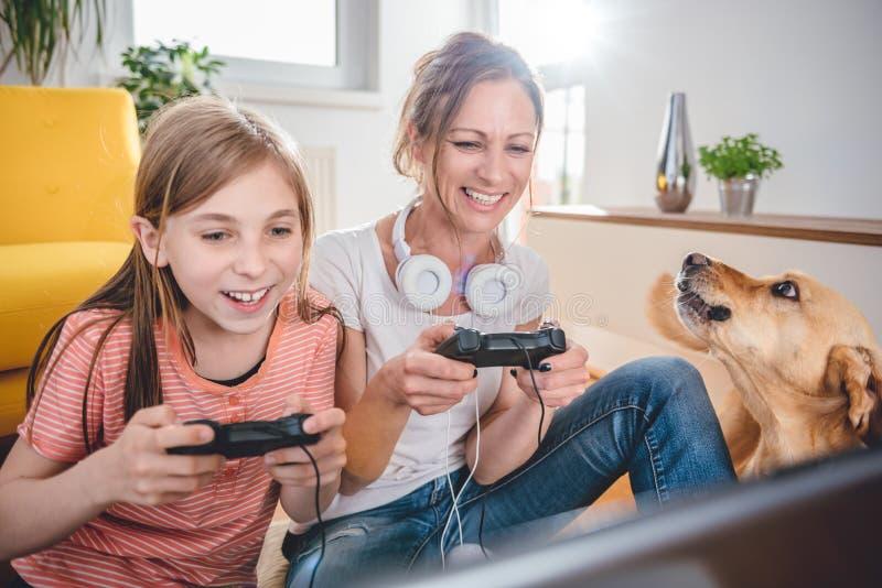 Mãe e filha que jogam jogos de vídeo foto de stock