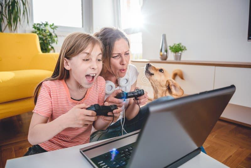 Mãe e filha que jogam jogos de vídeo foto de stock royalty free