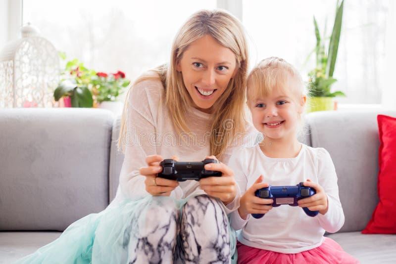 Mãe e filha que jogam jogos de vídeo na cama imagem de stock royalty free