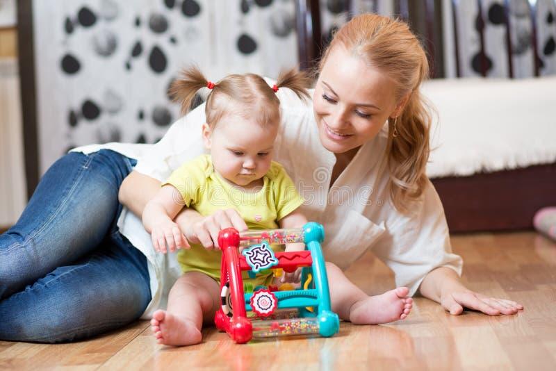 Mãe e filha que jogam junto com o brinquedo lógico colorido no assoalho de um quarto em casa fotos de stock