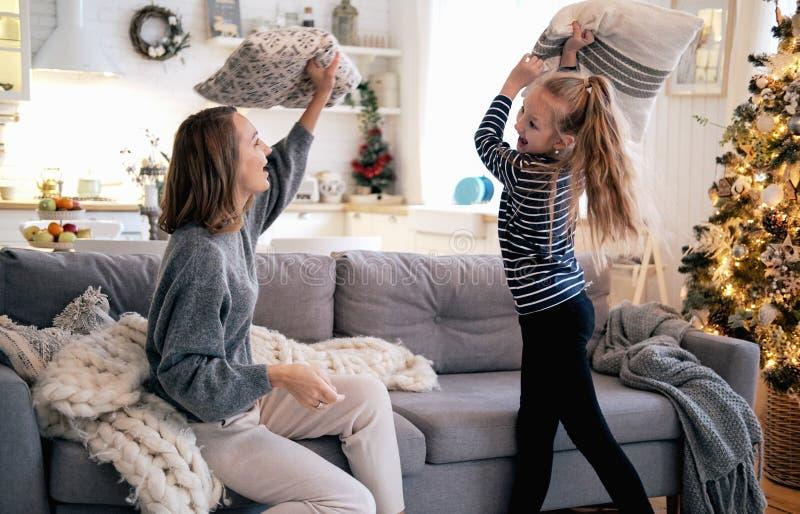 Mãe e filha que jogam a luta de descanso no sofá em casa imagens de stock