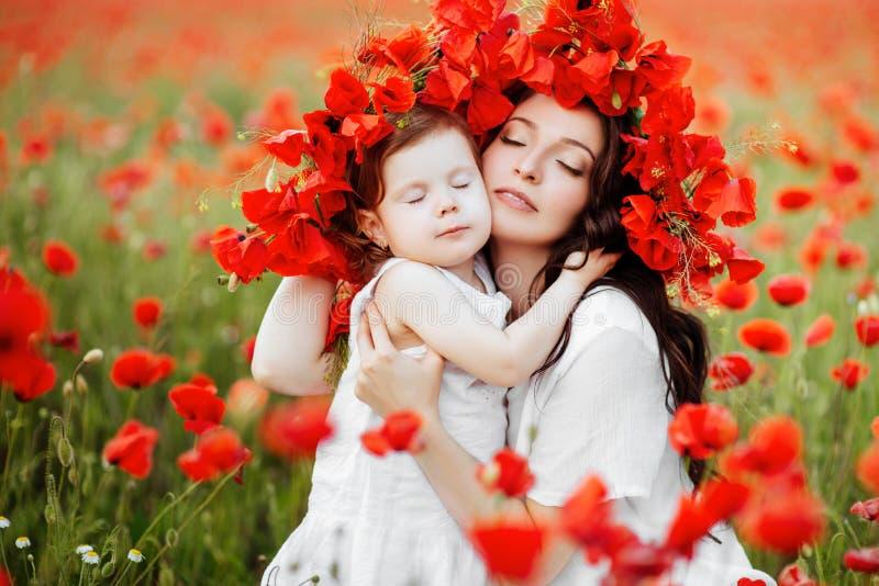 Mãe e filha que jogam no campo de flor fotografia de stock royalty free