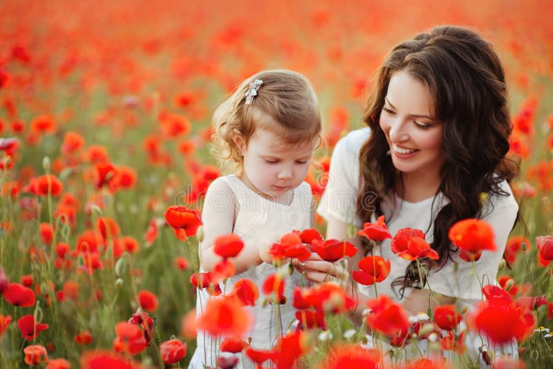 Mãe e filha que jogam no campo de flor imagens de stock royalty free