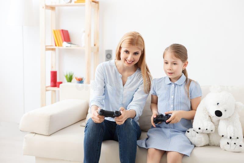 Mãe e filha que jogam no console fotografia de stock