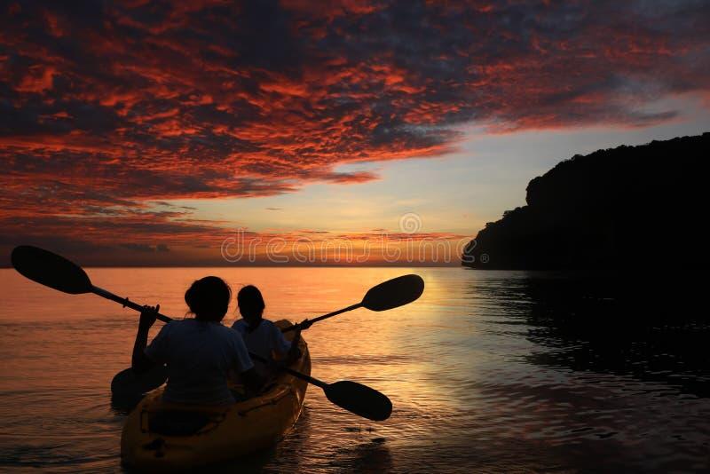Mãe e filha que kayaking no oceano com por do sol vermelho do céu imagens de stock