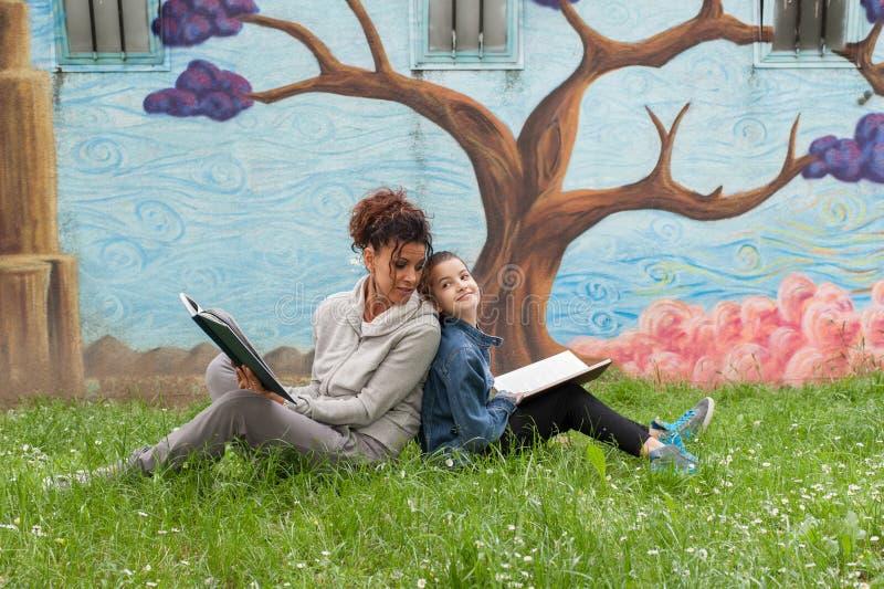 Mãe e filha que leem um livro imagens de stock