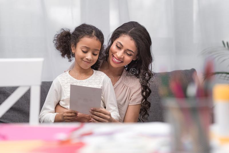 Mãe e filha que olham o cartão no dia de mães foto de stock
