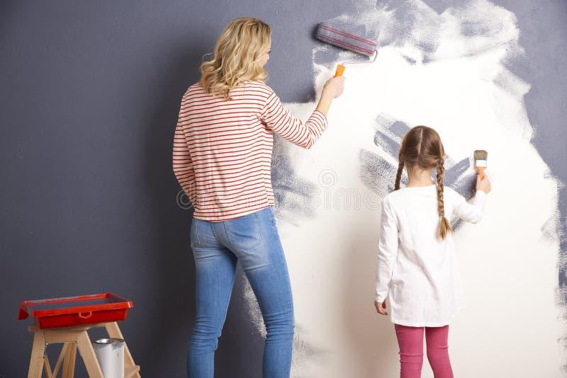 Mãe e filha que pintam sua casa nova fotografia de stock