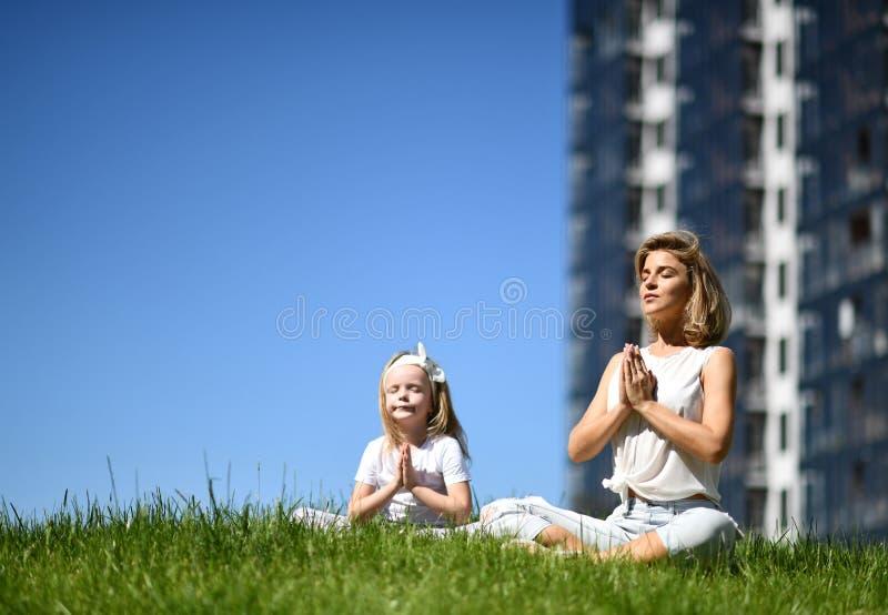 Mãe e filha que praticam junto a ioga fora em uma cidade urbana da grama junto imagem de stock