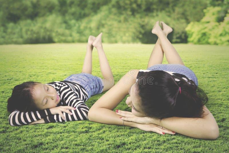 Mãe e filha que relaxam no prado foto de stock