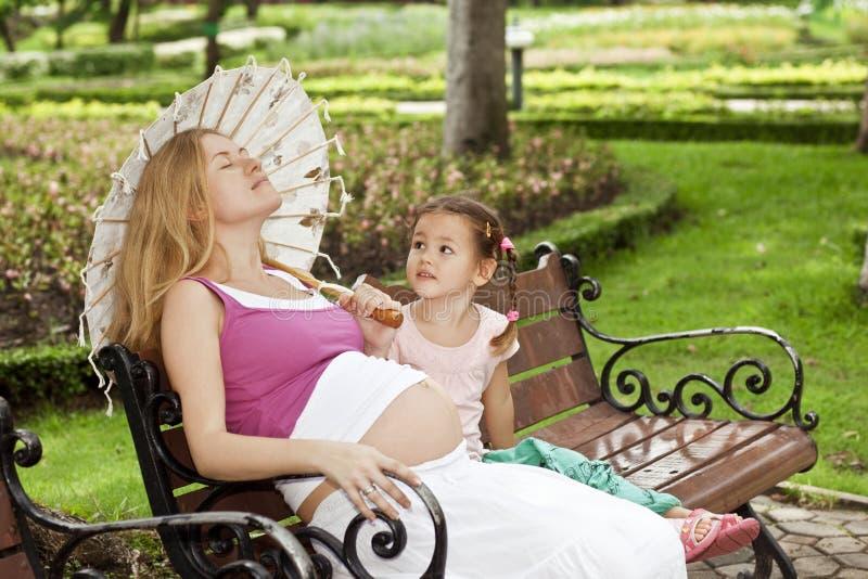 Mãe e filha que sentam-se em um banco de parque fotos de stock royalty free