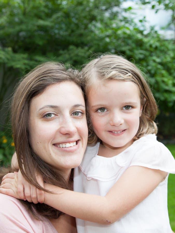 Mãe e filha que sentam-se junto na grama verde fotografia de stock