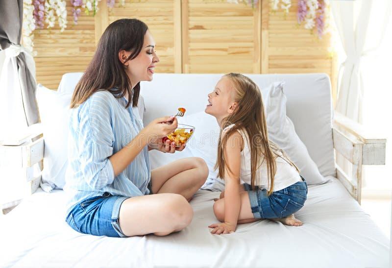 Mãe e filha que sentam-se na cama em casa que come o café da manhã foto de stock royalty free