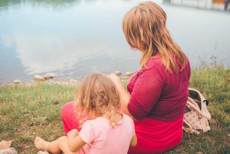 Mãe e filha que sentam-se na praia em um dia de verão agradável imagem de stock